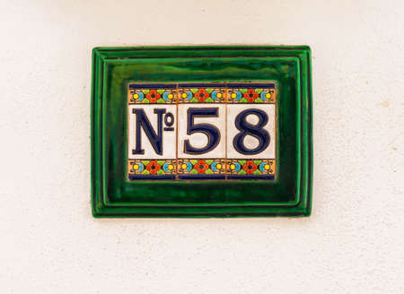 Decorative ceramic house number 58 tile on the wall, characteristic decorative element, number Фото со стока