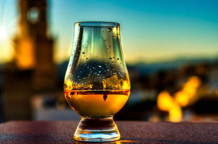 Expensive single malt whiskey in the rays of the setting sun, in the background a picturesque Spanish town with a church tower, relax with unique whiskey