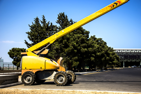 Lifting crane yellow on wheels for lifting a person