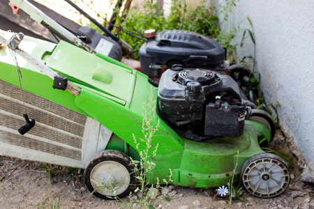 Lawn mowers lie near the wall in the early morning Stock Photo