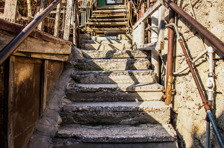 An old staircase with an iron rusty banister