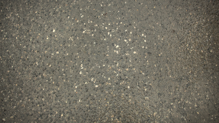 Background texture of wet dark asphalt in the early morning