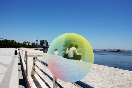 Loving couple in a glass bowl by the sea on Primorsky Boulevard of Baku