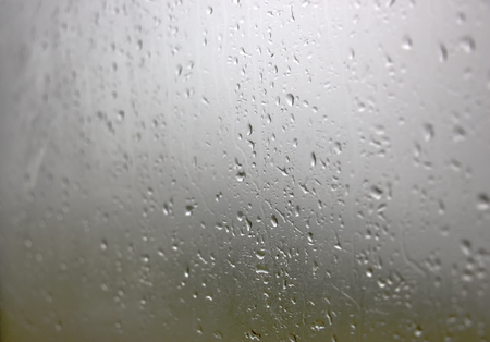 Rain drops on window glasses surface with cloudy background . Natural Pattern of raindrops isolated on cloudy background. Imagens