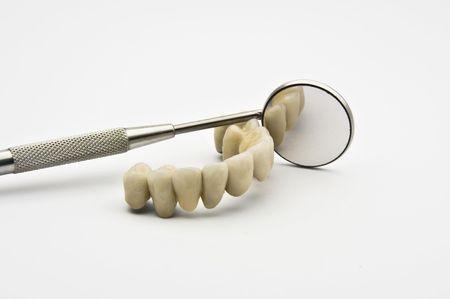 Prothèses dentaires avec miroir dentaire sur fond blanc