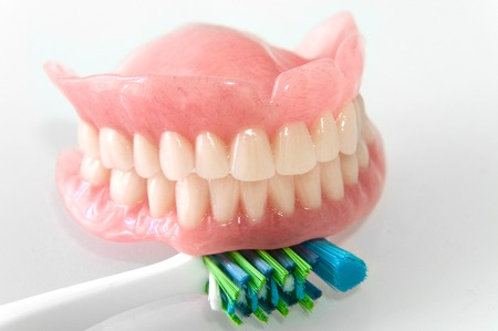 periodontics: Acrylic dentures with toothbrush on white background