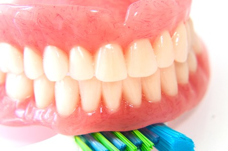 surrogate: Acrylic dentures with toothbrush on white background