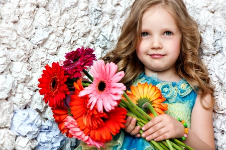 Fashion baby face beautiful child with fair hair in a pink dress holds flowers