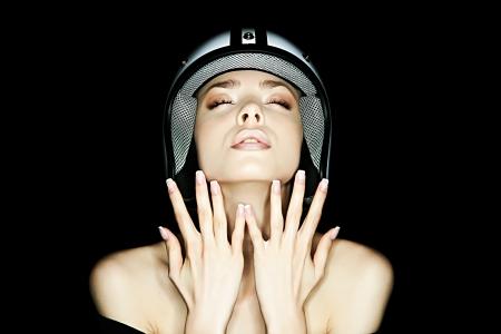 hermosa niña en casco de moto plantea cámara frontal