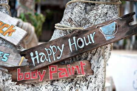 happy hour, body paint board notices on tree trunk photo