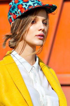 color model: color bright  woman fashion model outdoor portrait in yellow coat