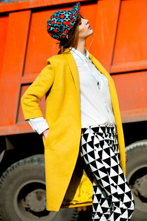 color bright  woman fashion model outdoor portrait in yellow coat