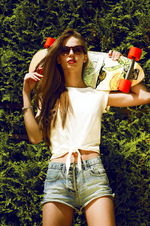 longboard: Girl in sunglasses poses with longboard
