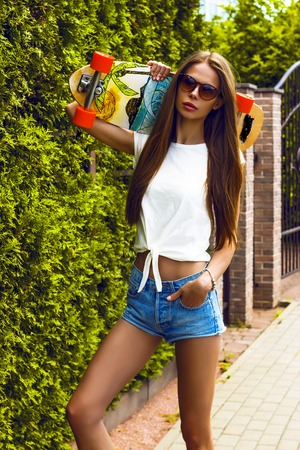 stylish girl: Stylish girl in sunglasses poses with longboard