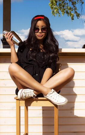 sits on a chair: Beautiful asian woman in cap and sunglusses sits on chair