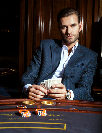 Handsome guy in blue classical suit plays cards