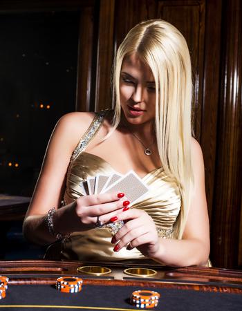 Blonde woman in elegant dress plays poker