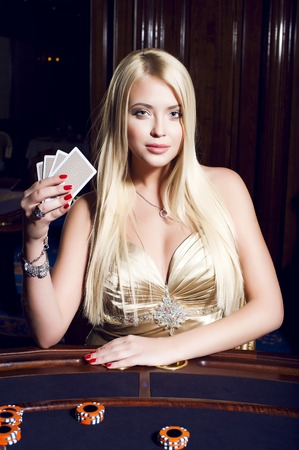 poker card: Blonde woman in elegant dress plays poker