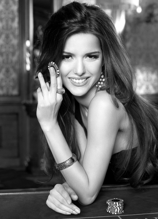 Beautiful brunette with long hair and charming smile in black evening dress plays in casino.Fashion look. Stock Photo