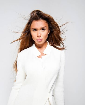 full lips: Portrait of beautiful woman with full lips and long hair poses in white coat on grey background.Studio.Perfect clean skin. Stock Photo