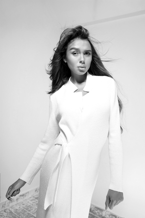 full lips: Beautiful woman with full lips and long hair poses in white coat on grey .Studio.Perfect clean skin.
