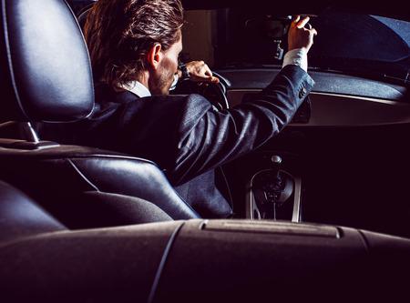 Man with beard in suit driving car Foto de archivo