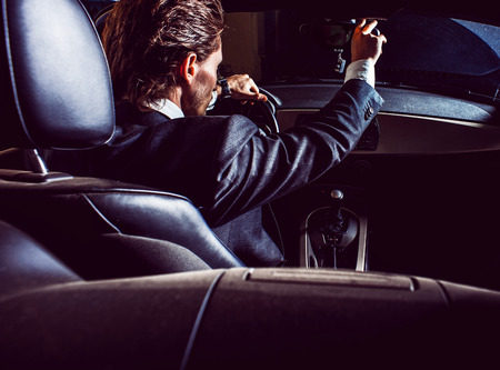 Man with beard in suit driving car Stock Photo