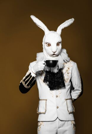 Actor posing in white rabbit suit with cup on dark background
