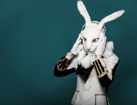 Actor posing in white rabbit suit with earphones on  black background Stock Photo