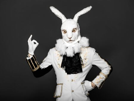 Actor posing in white rabbit suit on black background.Studio shot