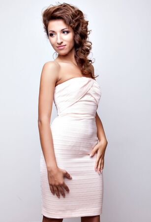 Beautiful woman with long curly hair in elegant stylish dress posing on white studio background Stock Photo