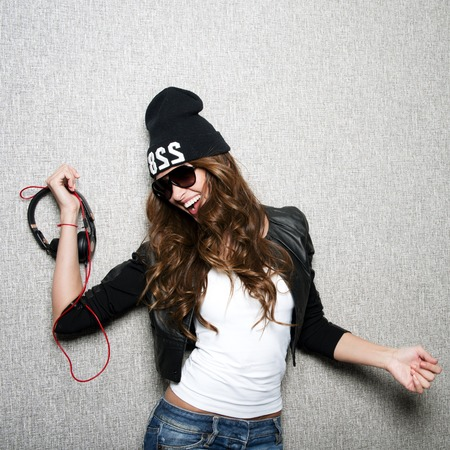 Portrait of beautiful long haired girl with earphones in stylish sunglasses,black cap,white shirt,black jacket and jeans poses on grey background