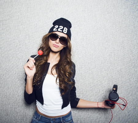Portrait of beautiful long haired girl with lollipop and earphones in stylish sunglasses,black cap,white shirt,black jacket and jeans poses on grey background Stock Photo
