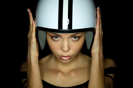 gesticulating: Portrait of beautiful young woman in shirt,white helmet pictured with star and stripes poses gesticulating arms on black background.Studio shot.Fashion look.Perfect clean skin. Stock Photo