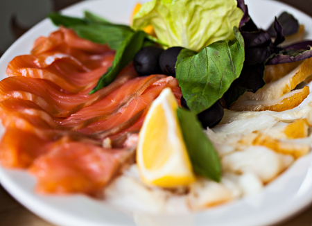 Fish appetizer with lemon and lettuce on white plate in restaurant