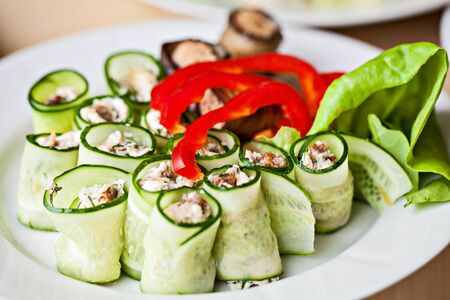 White plate of vegetable snacks.Eggplant cucmber Rolls with pepper and lettuce