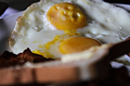 White plate of tasty fried egg with bacon and fresh bread