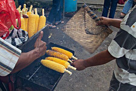 Asian man roasts and sells corn on street near beach