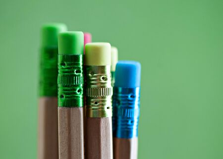 Row of color pencils on green  background
