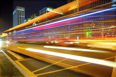 urban life: High speed and blurred bus light trails in downtown nightscape Stock Photo