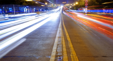 High speed traffic and blurred light trails in downtown night-scape