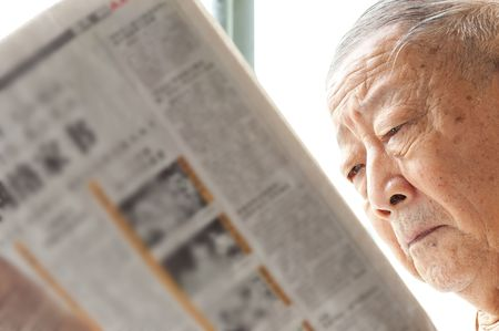 a senior man is reading newspaper intently    photo