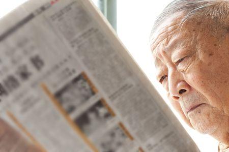 periodicos: un hombre senior est� leyendo el peri�dico atentamente  Foto de archivo