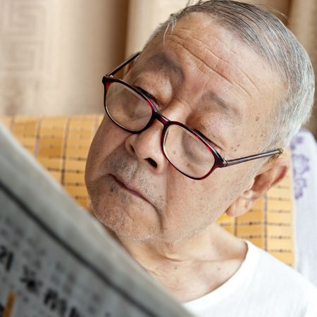 reading newspaper: a senior man is reading newspaper intently   Stock Photo