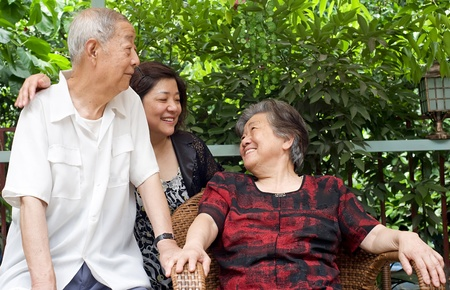 kindly: a happy senior couple and their daughter