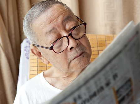 reading newspaper: a senior man is reading newspaper
