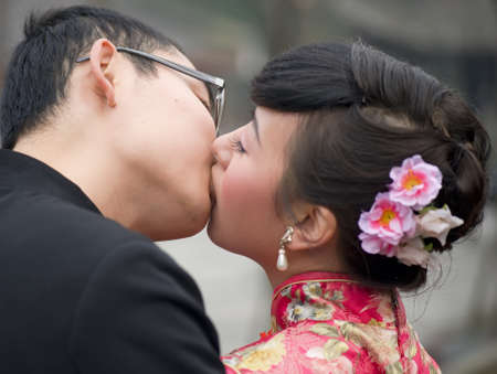 a young couple embracing and kissing on their wedding day photo