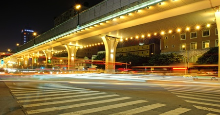 flyover: High-speed vehicles bright light trails on urban roads under overpass at night Stock Photo