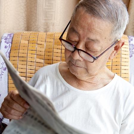 a senior man is reading newspaper photo