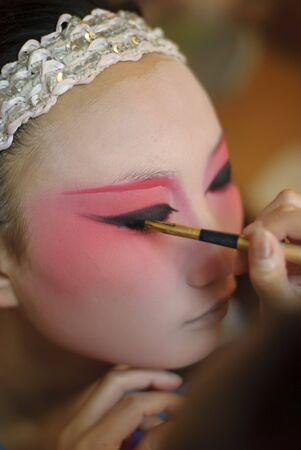 Chinese opera actress is painting her face backstage photo